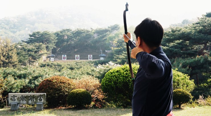 An archer aims at a target 145 meters away at Sukhojung, a traditional Korean archery range, on Mount Nam in Seoul. At the bottom left is a stone carved with Chinese characters that read: 'Don't speak and mind your manners when shooting arrows.' / Courtesy of Sukhojung