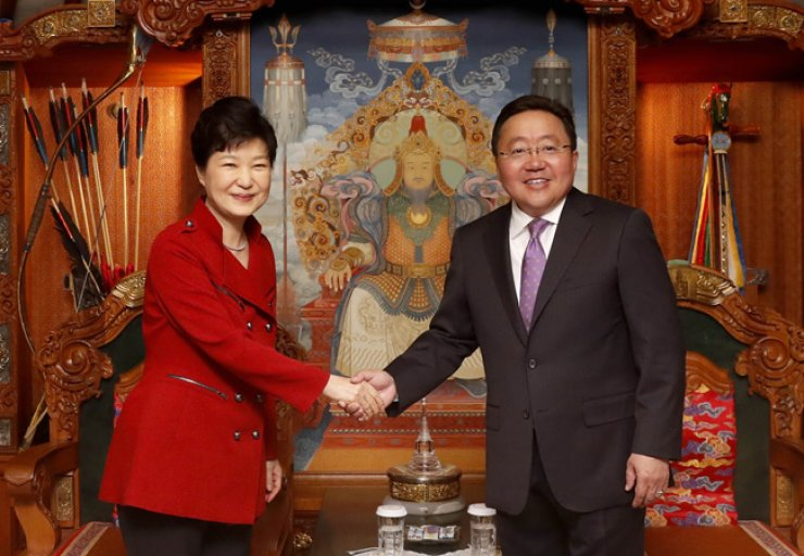 President Park Geun-hye shakes hands with her Mongolian counterpart Tsakhiagiin Elbegdorj before their summit in Ulaanbaatar, Sunday. The two agreed to seek a free trade pact to expand bilateral economic cooperation, according to Cheong Wa Dae. / Yonhap