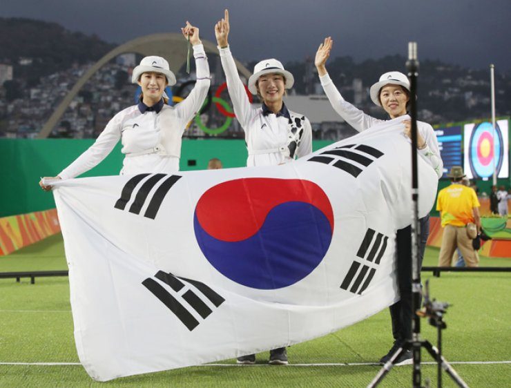 (From left) South Korea's Ki Bo-bae, Choi Mi-sun and Chang Hye-jin won gold in the women's team archery competition on Aug. 7. / Yonhap
