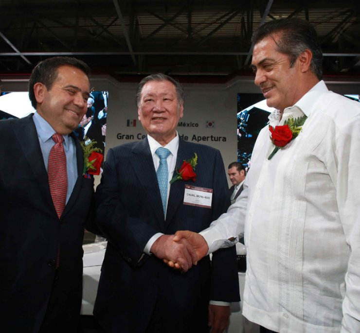 Hyundai Motor Group Chairman Chung Mong-koo, center, shakes hands with Nuevo Leon State Governor Jaime Rodriguez Calderon during a ceremony celebrating the completion of Kia Motors new factory in Pesqueria, Nuevo Leon, northern Mexico, Thursday. / Courtesy of Hyundai Motor