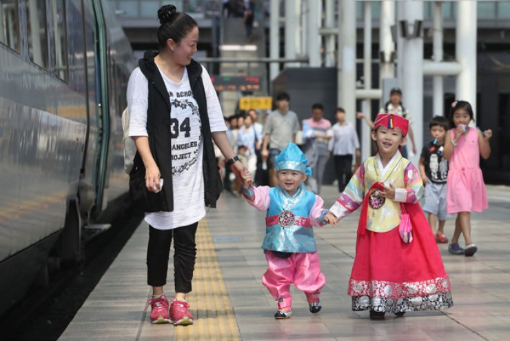 A family, with the children clad in traditional Korean attire, or hanbok, heads to board a train bound to the parents' hometown at Seoul Station, Tuesday, ahead of Chuseok, which falls on Thursday. / Yonhap