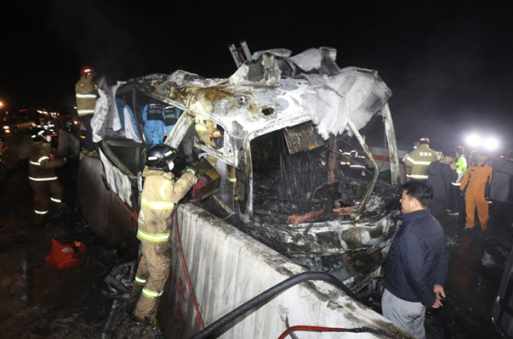 Firefighters examine a tour bus that caught fire on an expressway in Ulsan, early Friday morning. The fire killed 10 passengers and injured seven. / Yonhap