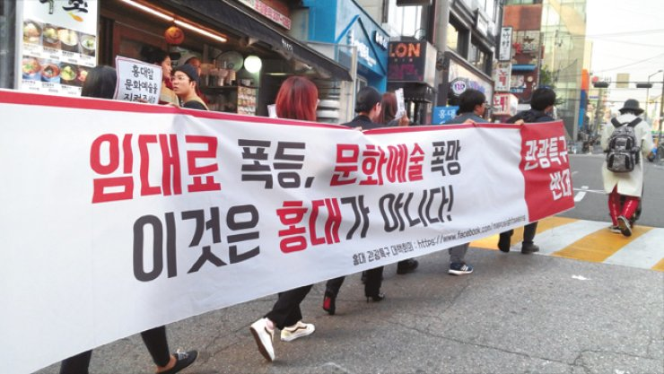 Artists and residents based in Hongdae walk in a protest, Wednesday, against Mapo-gu Office which plans to designate the area a 'special tourist zone.' The banner says 'Skyrocketing monthly rent, collapsing art culture. This is Not Hongdae!' / Korea Times photo by Choi Ha-young