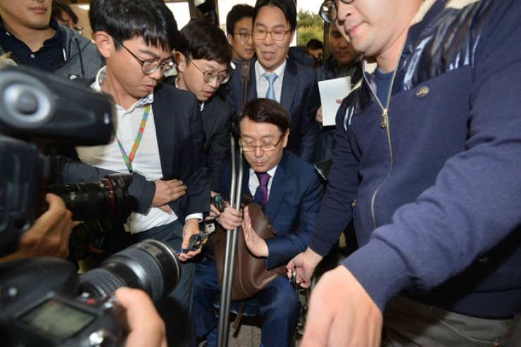 Yonsei University Professor Kim Hyung-su, in a wheelchair, is surrounded by reporters at the Seoul Central District Prosecutors' Office in southern Seoul, Sunday, before being questioned over the scandal-ridden Mir Foundation, of which he was the inaugural head. The foundation and K-Sports Foundation are allegedly linked to President Park Geun-hye's close aides. / Yonhap