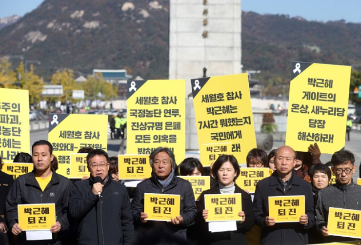 Bereaved family members of the Sewol ferry disaster victims and members of civic groups demand President Park Geun-hye reveal the truth about the sinking, including where she was during the first seven hours after the accident, as well as for her to take responsibility for the scandal involving her confidant Choi Soon-sil, during a press conference at Gwanghwamun Square in downtown Seoul, Tuesday. / Yonhap