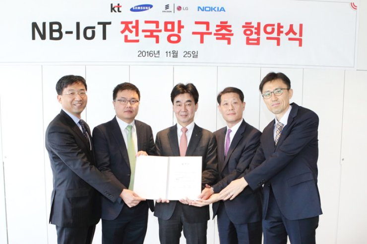 KT's network strategy unit Senior Vice President Seo Chang-seok, left, and KT's supply chain management strategy unit Chief Procurement Officer Hahn Won-sic, center, pose with executives of the telecom company's network equipment providing partners Samsung Electronics, Ericsson-LG and Nokia at the company's office in Gwanghwamun, central Seoul, Friday, after signing an agreement to cooperate in establishing a nationwide narrowband Internet of Things network. / Courtesy of KT