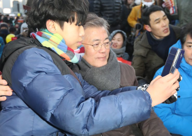 Moon Jae-in, a former leader of the main opposition Democratic Party of Korea, poses for a selfie with a citizen at a candlelit rally in central Seoul, Saturday, where people gathered to call for the immediate resignation of President Park Geun-hye. / Yonhap