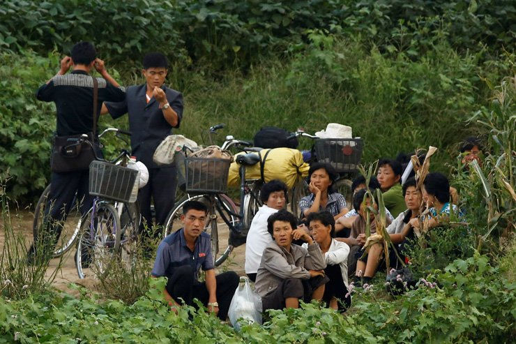 In this file photo from last September, North Koreans wait for a boat that travels along the Yalu River ― also known as Amnokgang River in South Korea ― between the North Korean city of Sinuiju and Dandong in China. / Yonhap