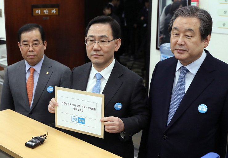 Bareun Party's floor leader Rep. Joo Ho-young, center, and other party members submit a joint motion to the National Assembly, Tuesday, to urge China to stop its economic retaliation against Korea over the deployment of the U.S. Terminal High Altitude Area Defense battery. / Yonhap