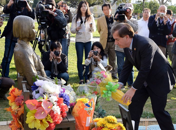 House Foreign Affairs Committee Chairman Ed Royce places a bouquet on a bench next to the bronze comfort woman statue in Glendale, California, in January 2014. / Korea Times file