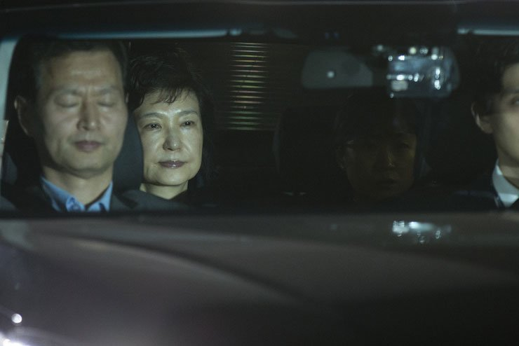 Former President Park Geun-hye sits with investigators in a sedan running into the Seoul Detention Center in Uiwang, Gyeonggi Province, early Friday. The court accepted the prosecution's request to arrest her on multiple charges, including bribery, abuse of authority, coercion and leaking government secrets. / Korea Times photo by Choi Won-suk