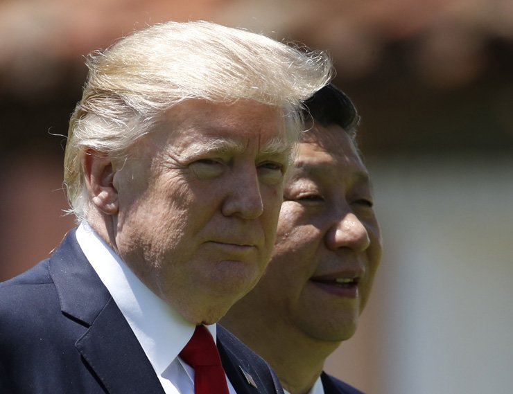 U.S. President Donald Trump, left, and Chinese President Xi Jinping walk together at Mar-a-Lago in Palm Beach, Fla. The U.S. is piling the pressure on Beijing to use its clout with North Korea to rein in its nuclear and missile programs. / AP-Yonhap