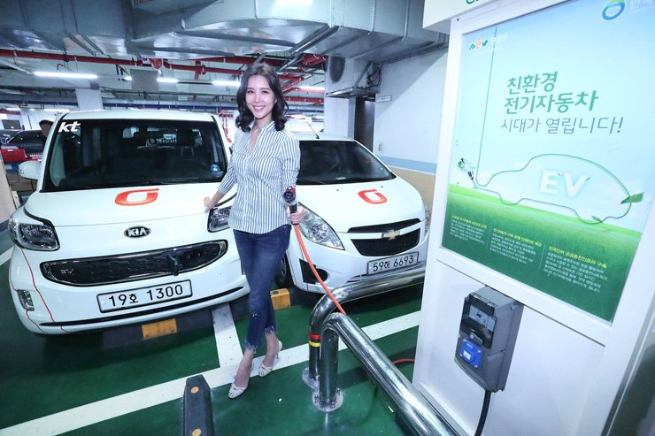 A model poses with KT's electric vehicles and charger at its headquarters in Seoul. Courtesy of KT