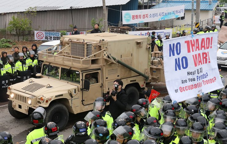 A military vehicle carrying parts of a U.S. Terminal High Altitude Area Defense (THAAD) system moves to a golf course in Seongju County, North Gyeongsang Province, Wednesday, while police confront local residents protesting the deployment. The U.S. Forces Korea pushed for an overnight operation to transport THAAD elements including its radar to the site to begin the controversial installation. / Yonhap