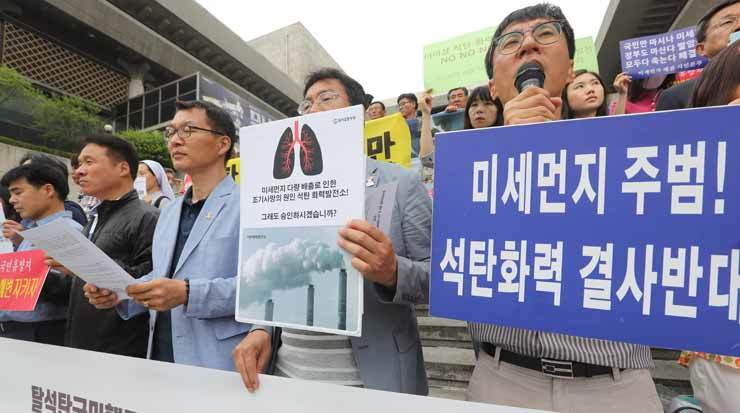 People from rural towns near coal-fired power plants listen to a speaker, Thursday, during a protest in Seoul against 10 new power plants to come near their villages./Yonhap