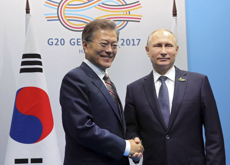 President Moon Jae-in, left, shakes hands with Russian President Vladimir Putin on the sidlelines of the G-20 summit in Hamburg Germany, Saturday. / Reuters-Yonhap