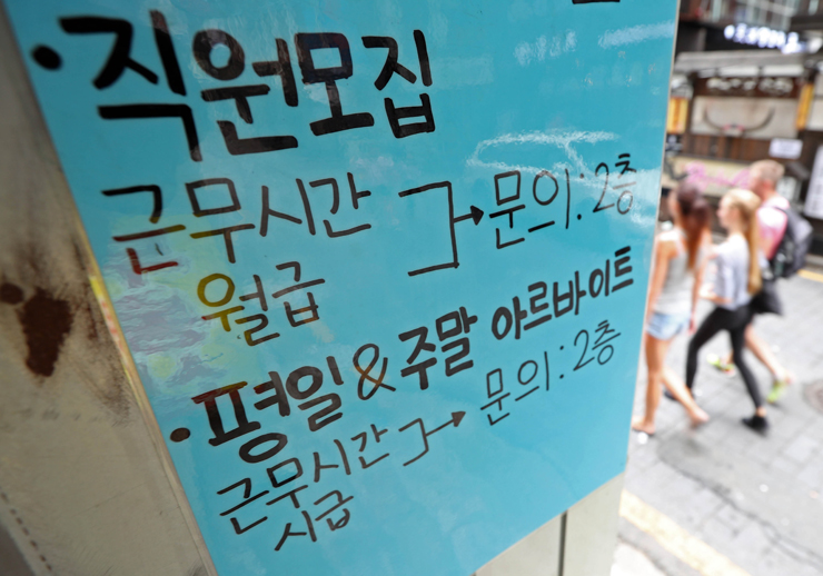 An employee works at a franchised restaurant in Seoul, Monday, one day after Korea decided to increase the minimum wage to 7,530 won in 2018. / Yonhap