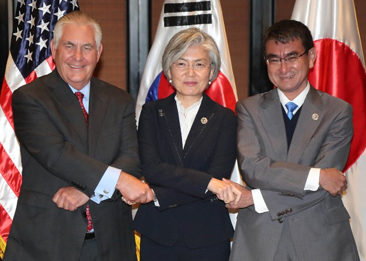 Foreign Minister Kang Kyung-wha, center, holds hands together with U.S. Secretary of State Rex Tillerson, left, and Japanese Foreign Minister Taro Kono during their joint talks on the sidelines of the ASEAN Regional Forum in Manila, the Philippines, Monday. / Yonhap