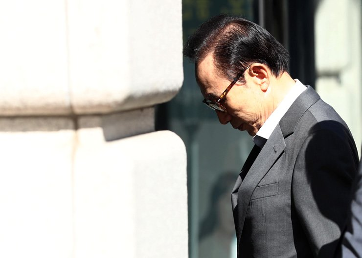 Former President Lee Myung-bak looks down while walking into his office building in Gangnam, Seoul, Sept. 29. He criticized the Moon Jae-in government for its policy aimed to eradicate 'deep-rooted social evils,' which he called political retaliation, on Facebook earlier in the day. / Yonhap