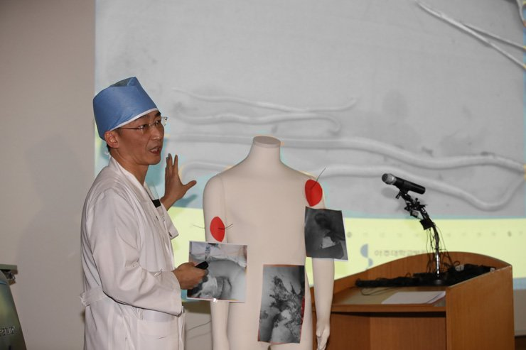 Trauma surgeon Lee Cook-jong shows images of parasitic worms found in a wounded North Korean soldier at Ajou University Hospital in Suwon, Gyeonggi Province, Nov. 15. The soldier was shot several times during his escape to the South Korean side of the Joint Security Area before undergoing emergency surgery at the hospital. / Yonhap
