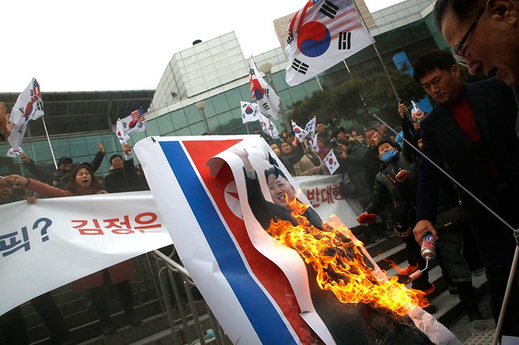 A conservative activist sets fire to a picture of North Korean leader Kim Jong-un and the North's flag in front of Seoul Station Monday in protest against the North's participation in the PyeongChang Winter Olympics. / Korea Times photo by Shim Hyun-chul
