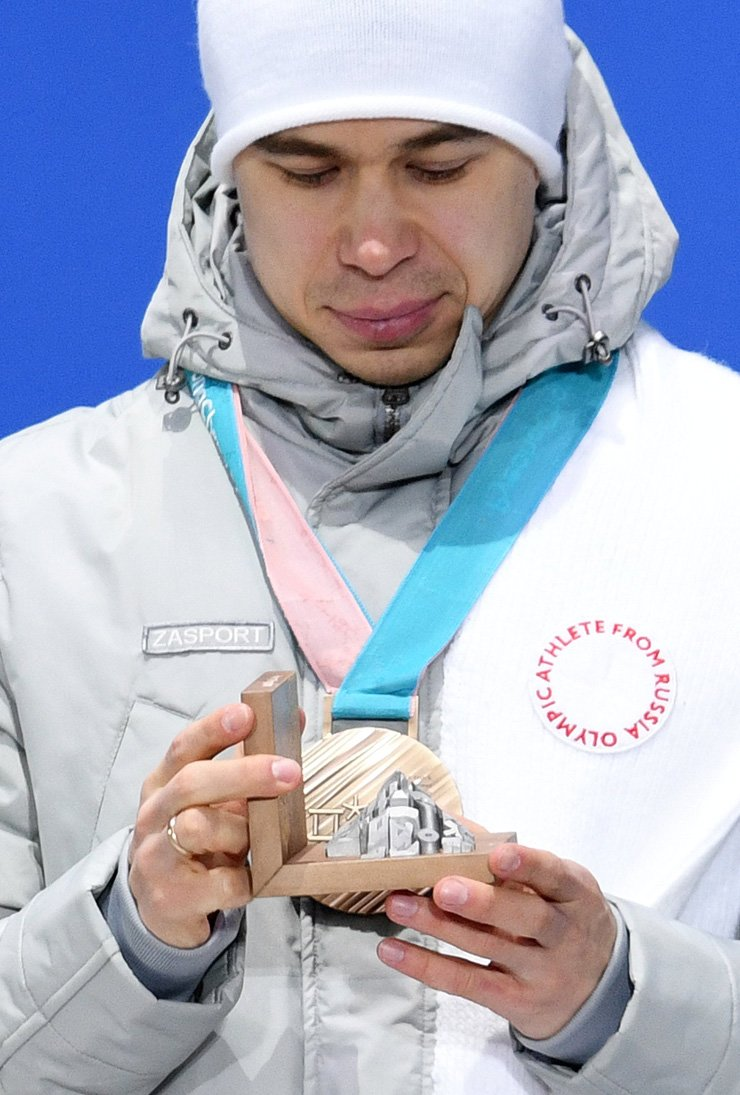 Semen Elistratov, an Olympic Athlete from Russia (OAR), wears a plain grey-white down coat and white hat in accordance with International Olympic Committee (IOC) guidelines on OAR competitors during a medal ceremony for the men's 1,500-meter short track speed skating at the PyeongChang Winter Olympics, Sunday. The IOC guidelines prohibit 168 Russian athletes from wearing any Russian symbols in line with its suspension of the country from joining the PyeongChang Olympics over its state-backed doping program. / EPA-Yonhap
