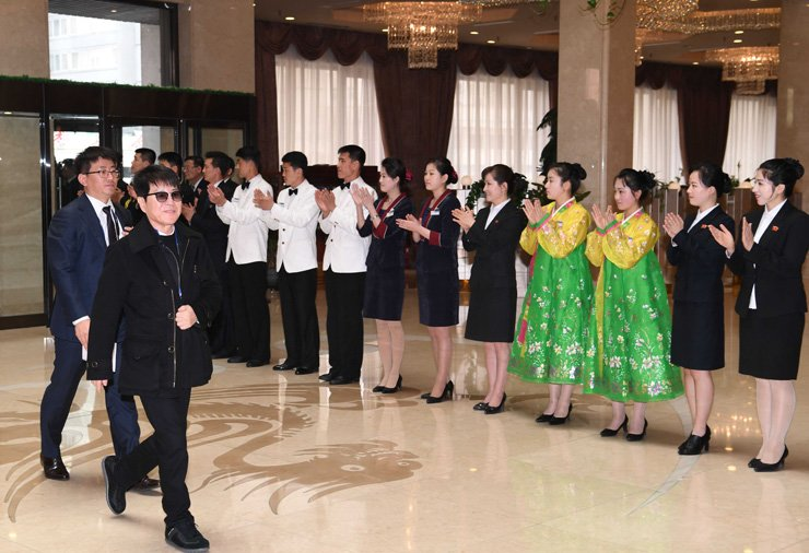 Cho Yong-pil, right front, one of South Korea's most influential pop singers, is greeted by staff of the Koryo Hotel in Pyongyang, March 31. Cho is among 120 members of a performance troupe from Seoul visiting the North. / Joint Press Corps