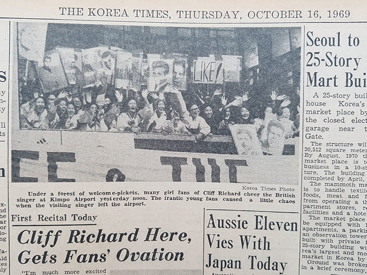The Korea Times published this photo on Oct. 16, 1969, captioned, 'Under a forest of welcome-pickets, many girl fans of Cliff Richard cheer the British singer at Kimpo Airport yesterday noon. The frantic young fans caused a little chaos when the visiting singer left the airport.' / Korea Times