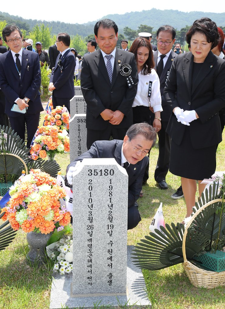 President Moon Jae-in touches the tombstone of Park Kyung-soo, one of the 46 South Korean soldiers killed in North Korea's torpedo attack on the Navy frigate Cheonan in March 2010, after attending a ceremony for the 63rd Memorial Day at Daejeon National Cemetery, Wednesday. / Yonhap