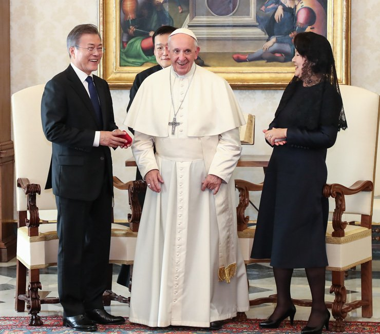 President Moon Jae-in smiles after receiving a rosary case from Pope Francis as a gift during their meeting at the Vatican Thursday. At right is first lady Kim Jung-sook. Moon and Kim are both Catholics. / Yonhap.