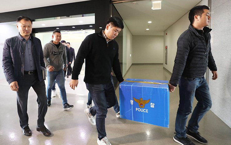 Investigators from the Gyeonggi Nambu Provincial Police Agency carry seized materials from their search of the office of WeDisk, a company owned by Yang Jin-ho, an IT CEO, in Bundang, Seongnam, Gyeonggi Province, Friday. Yang is accused of abusing and assaulting workers. / Yonhap