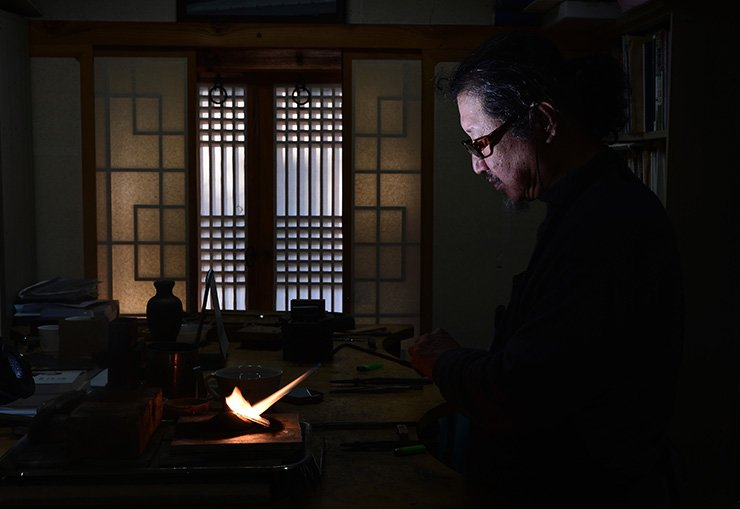 Kwack Hong-chan, a third-generation traditional metal artisan, shows the process of creating a traditional metal work in his workshop in Bucheon, Gyeonggi Province. Kwack carves on the surface of silver artifacts or other metal ornaments using a fine chisel, or inlays gold, silver or blackened copper threads in the grooves to make various patterns. Korea Times photo by Shim Hyun-chul