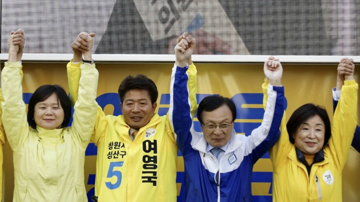 Yeo Young-guk, second from left, a candidate from the liberal Justice Party, holds hands together with Democratic Party of Korea Chairman Lee Hae-chan, second from right and Justice Party Chairwoman Lee Jeong-mi, left, calling for support during a street campaign in Changwon, South Gyeongsang Province, Tuesday. Korea Times photo by Shim Hyun-chul