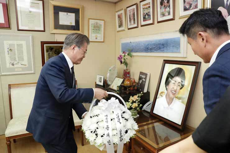 President Moon Jae-in places flowers in front of a portrait of the late former first lady Lee Hee-ho, the widow of former liberal President Kim Dae-jung, at her home in Donggyo-dong, Mapo District, Seoul, Sunday, after he arrived back in the capital following an eight-day tour of Finland, Norway and Sweden. Yonhap