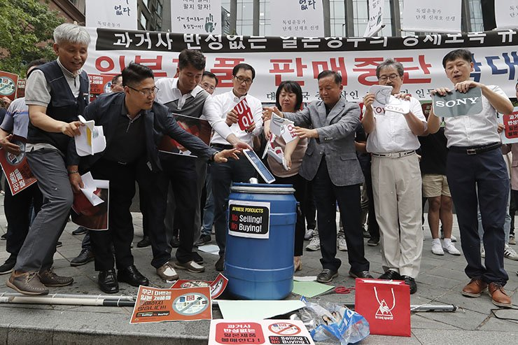 South Korean small and medium-sized business owners throw papers showing logos of major Japanese brands into a trash can during a rally calling for a boycott of Japanese products in front of the Japanese embassy in Seoul, South Korea, Monday, July 15, 2019. South Korea and Japan last Friday, July 12, failed to immediately resolve their dispute over Japanese export restrictions that could hurt South Korean technology companies, as Seoul called for an investigation by the United Nations or another international body. The signs read: 'Our supermarket does not sell Japanese products.' AP