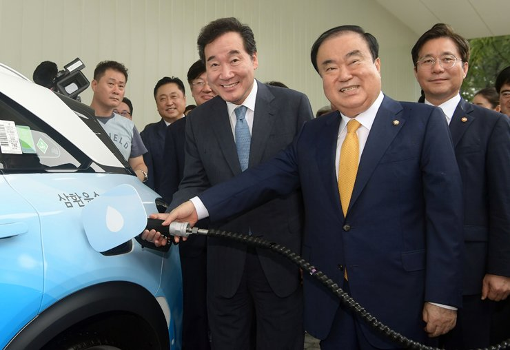 Prime Minister Lee Nak-yon, left, and National Assembly Speaker Moon Hee-sang fuel up a Nexo hydrogen taxi, Tuesday, at a hydrogen charging station installed at the National Assembly. The charging station, built by Hyundai Motor, is the first commercial hydrogen station in Seoul. Existing charging stations in Yangjae-dong and Sangam-dong are free but will start charging customers before the end of the year. Courtesy of Hyundai Motor