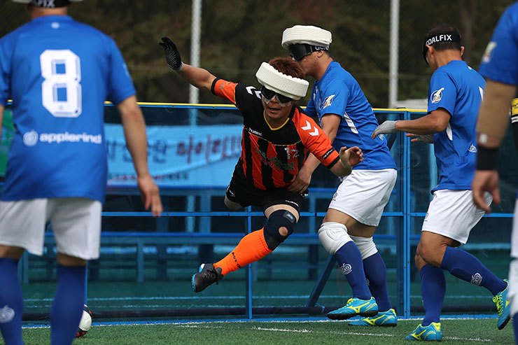 Blind football players compete for the ball in a B1 game between South Chungcheong Province (blue) and North Gyeongsang Province (orange) during the 39th annual National Sports Festival for the Disabled at a stadium in Sangam-dong, Seoul, Thursday. The South Chungcheong Province team won 2-1. Athletes in the B1 classification are totally or almost totally blind. They play by relying on bell sounds from the ball and the voices of their coaches. Korea Times photo by Choi Won-suk