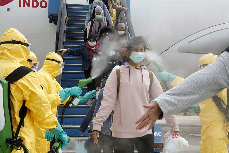 In this photo released by the Indonesian Foreign Ministry, Indonesians who arrived from Wuhan, China, are sprayed with antiseptic at Hang Nadim Airport in Batam, Indonesia Sunday, Feb. 2, 2020. Indonesians evacuated from Wuhan, the Chinese city at the center of a deadly virus outbreak, were transported to a quarantine zone on a remote island at the edge of the South China Sea, shortly after landing on Batam, an island near Singapore on Sunday morning. (Indonesian Foreign Ministry via AP)