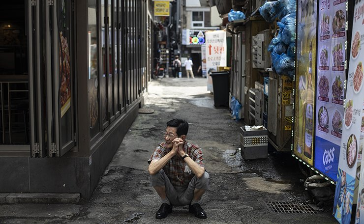 A restaurant owner squats in an empty street in Jongno 3-ga, July 30. The district, famous for its many eateries, usually bustles with office workers during lunch hour. Korea Times photo by Choi Won-suk