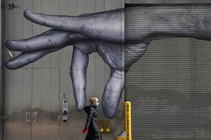 In this file photograph taken on April 22, 2020, a woman in a mask walks past a mural of a hand on the side of a building in Midtown, New York City.  AFP