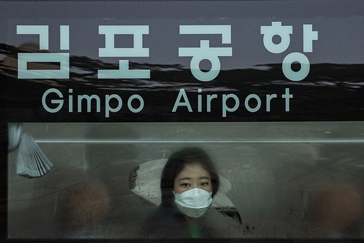 A woman wearing a face mask looks out at Gimpo International Airport on Jan. 31. Many Korean Chinese from Wuhan, a Chinese city which is believed to be the epicenter of the coronavirus as the first case was reported there, arrived in Seoul that day.  Korea Times photo by Shim Hyun-chul