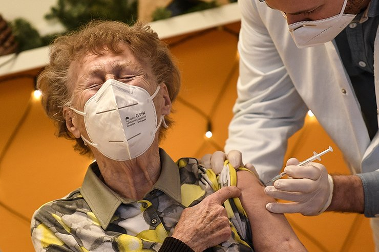 A resident of a nursing home reacts as she gets an injection of the COVID-19 vaccine in Cologne, Germany, Dec. 27. AP