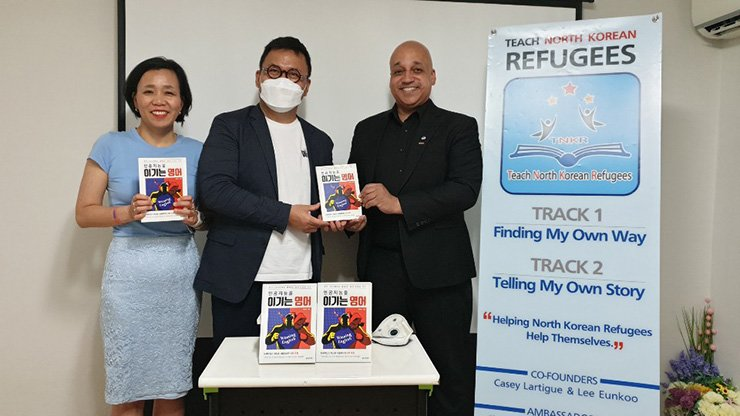 Park Min, center, CEO of PR agency ToGo Communication, holds a copy of the book 'Winning English' with Casey Lartigue Jr., co-founder of Teach North Korean Refugees (TNKR), a NGO offering educational services to North Korean refugees, in a donation ceremony at the NGO's office in Seoul, Thursday. To Park's left is Lee Eun-koo, co-founder of the NGO. Park donated 20 copies of the self-help book on how to learn English efficiently to TNKR to help North Korean refugees interested in learning English. The two organizations will seek collaboration in areas that meet their interests. Courtesy of TNKR
