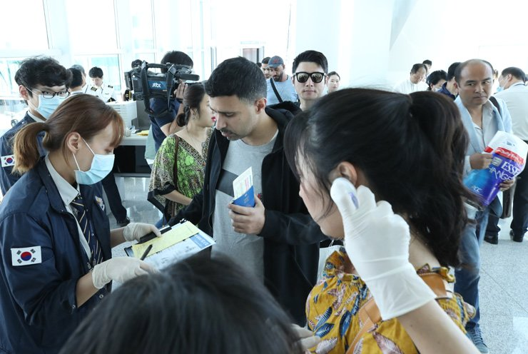 Quarantine officers ask health-related questions to travelers with high body temperature arriving from the United Arab Emirates, at Incheon International Airport, Monday, two days after a man was confirmed to have contracted Middle East Respiratory Syndrome (MERS) during a visit to Kuwait. / Yonhap