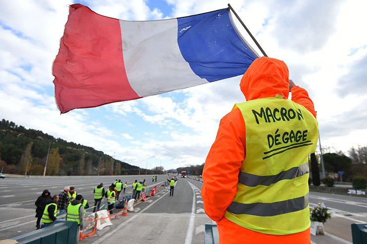 A man with a sign reading 'Macron resign' waves a French flag as 'yellow vests' (Gilets jaunes) protestors gather to protest against rising oil prices and living costs at the highway's toll of La Barque, on Dec. 9, near Marseille, southern France. AFP