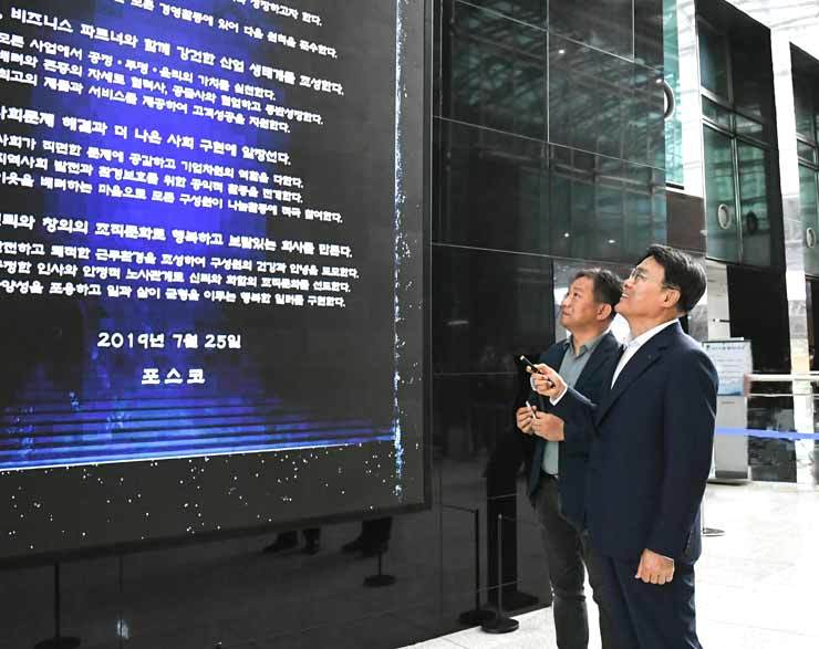 POSCO Chairman Choi Jeong-woo, right, looks at the corporate citizenship charter established at the POSCO center in Seoul, July 28. / Courtesy of POSCO
