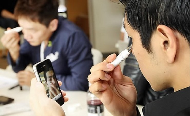 A man applines concealer on his face. / Yonhap