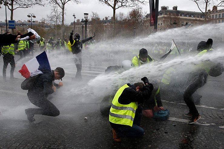 A French flag floats as fire is burning during a protest of Yellow vests (Gilets jaunes) against rising oil prices and living costs, on Dec. 1, in Paris. Speaking at the Paris police's command centre, French Prime Minister said 36,000 people were protesting across France, including 5,500 in the capital for this 3rd nationwide day of blockade ands demos. AFP
