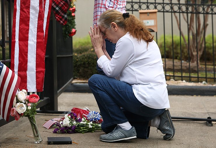 Suzette Renee Drab says a prayer after leaving a flower bouquet at the gate outside of former President George H.W. Bush's residence on Saturday in Houston. Bush, who died late Friday at his Houston home at age 94, is to be honored with a funeral service in the nation's capital on Wednesday, followed by burial Thursday at his presidential library in Texas. Houston Chronicle via AP