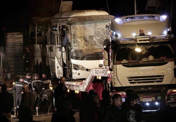 Security forces stand near a tourist bus after a roadside bomb in an area near the Giza Pyramids in Cairo, Egypt, Dec. 28. Egypt's Interior Ministry said in a statement that two Vietnamese tourists were killed and others wounded in the incident. AP